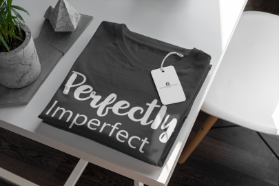mockup-of-a-t-shirt-with-a-clothing-tag-attached-displayed-on-a-minimalistic-table-379-el.png